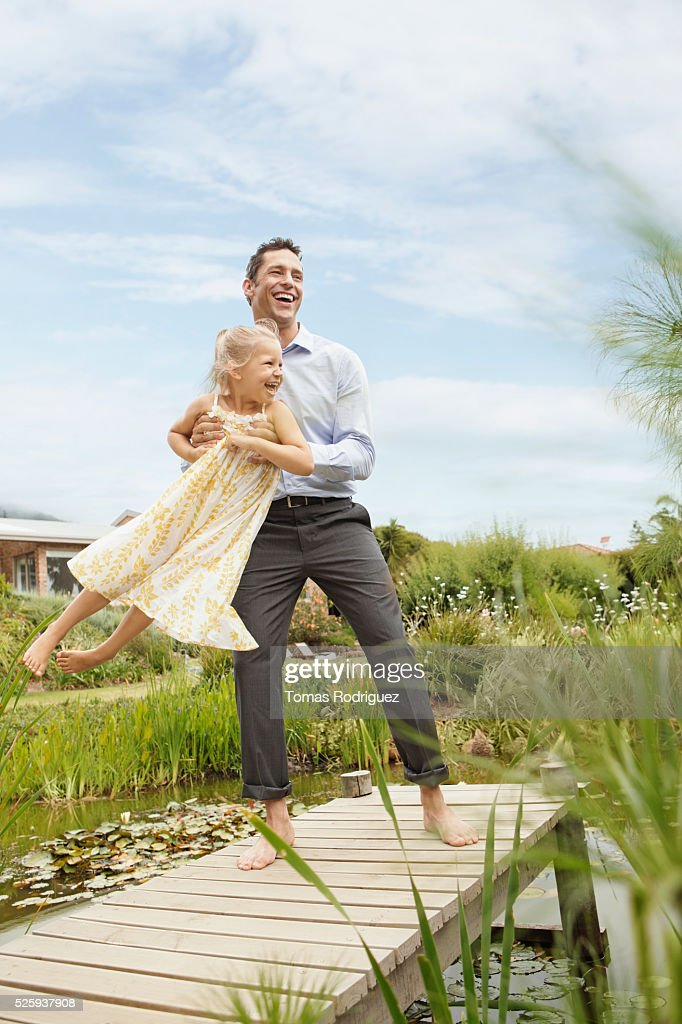 Father standing on jetty and holding daughter (4-5) : Stock Photo