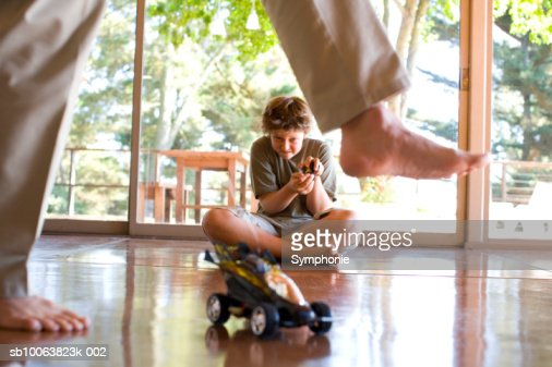Father stepping past son (10-11) playing with radio controlled car