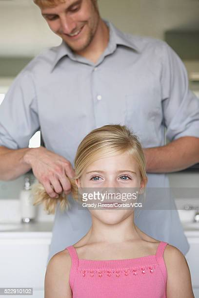 Father styling daughter's hair