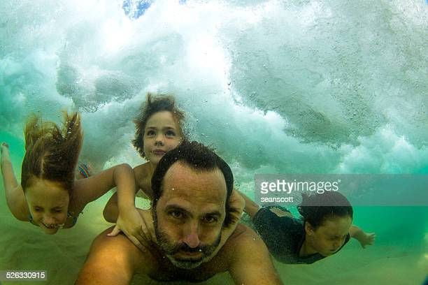 Father swimming underwater in the ocean with three children