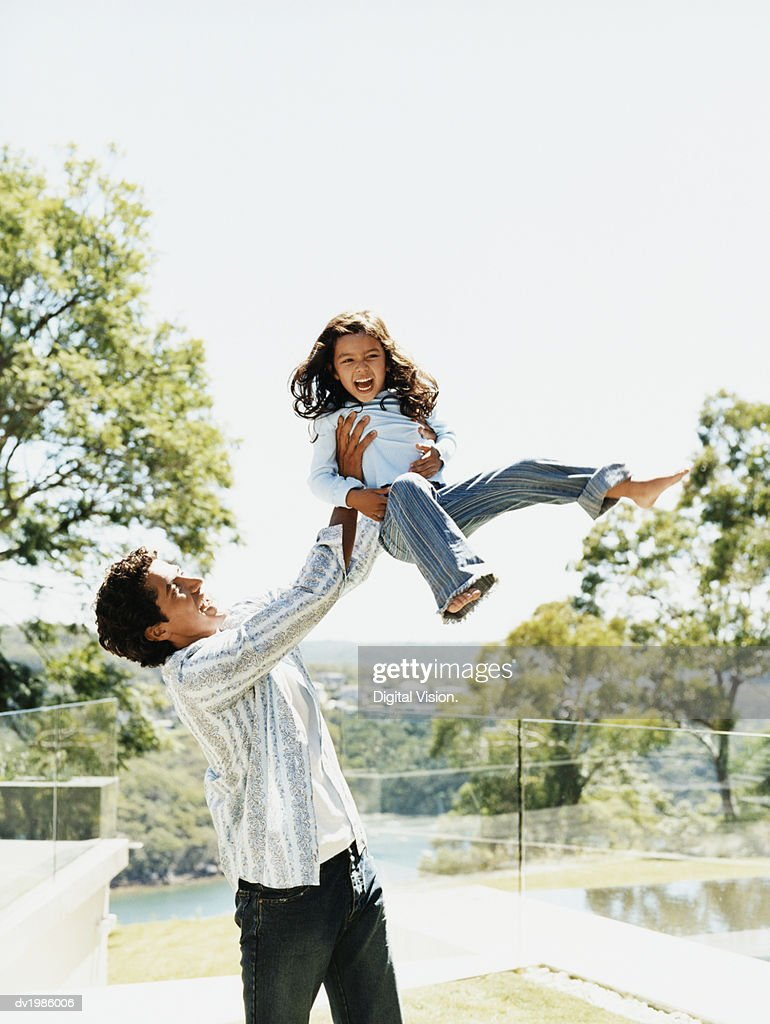 Father Swinging His Daughter in the Air : Stock Photo