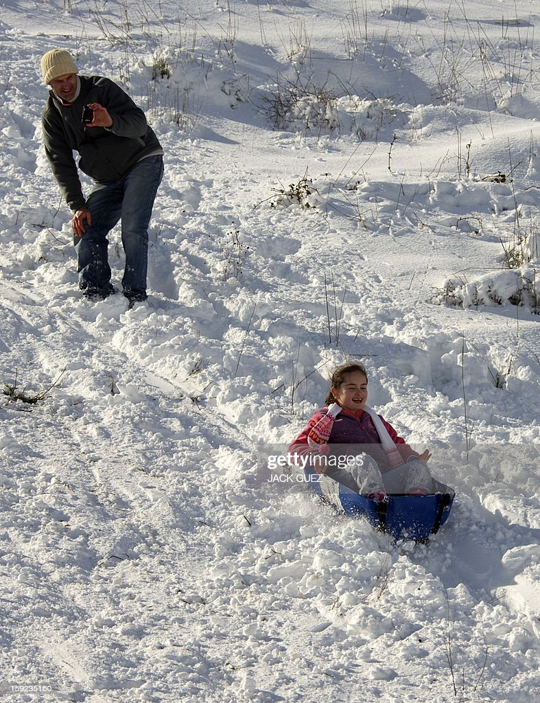 A father takes pictures of her daughter playing with a sledge in the Israeli occupied Golan Heights on January 10, 2013. The worst storms in a decade left the region under a blanket of snow. AFP PHOTO / JACK GUEZ