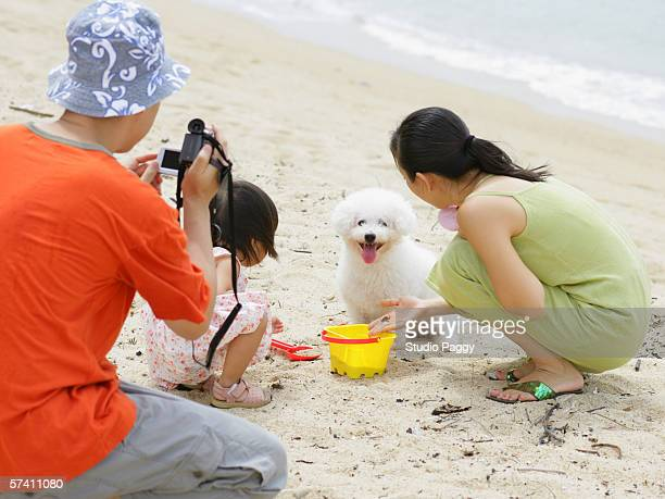 Father taking a picture of his wife and his daughter
