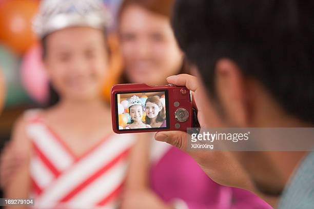 Father Taking a Picture of Mother and Daughter on Daughter's Birthday