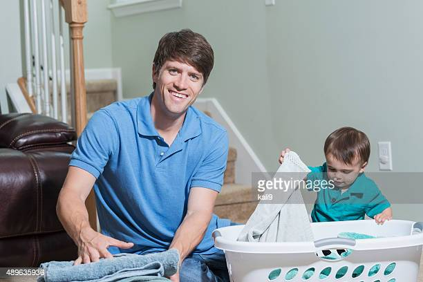 Father taking care of baby and folding laundry