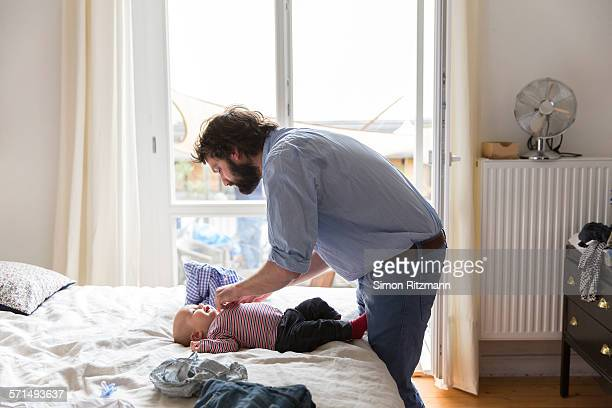 Father taking care of baby son at home