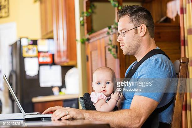 Father taking care of young daughter while working on laptop
