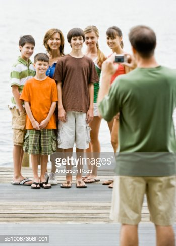 Father taking photograph of family on pier : Stock Photo