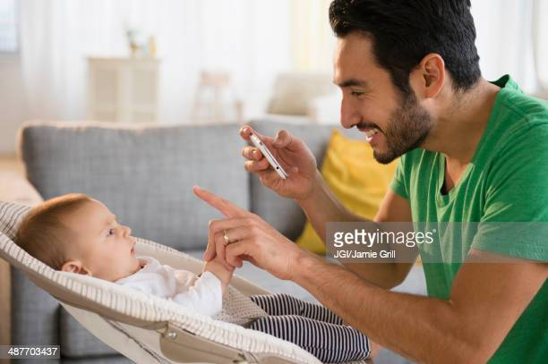 Father taking pictures of baby