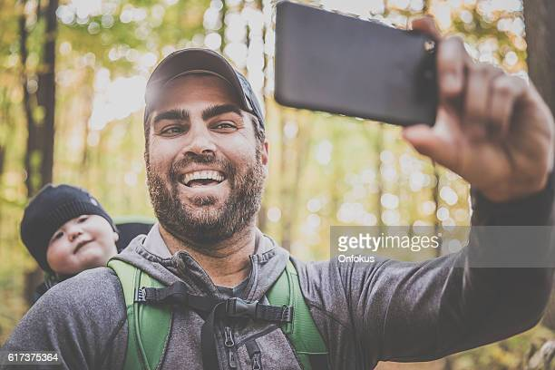 Father Taking Selfie with Baby in Forest
