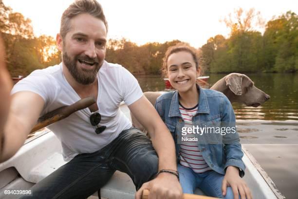 Vater unter Selfie mit Tochter und Hund im Ruderboot am See