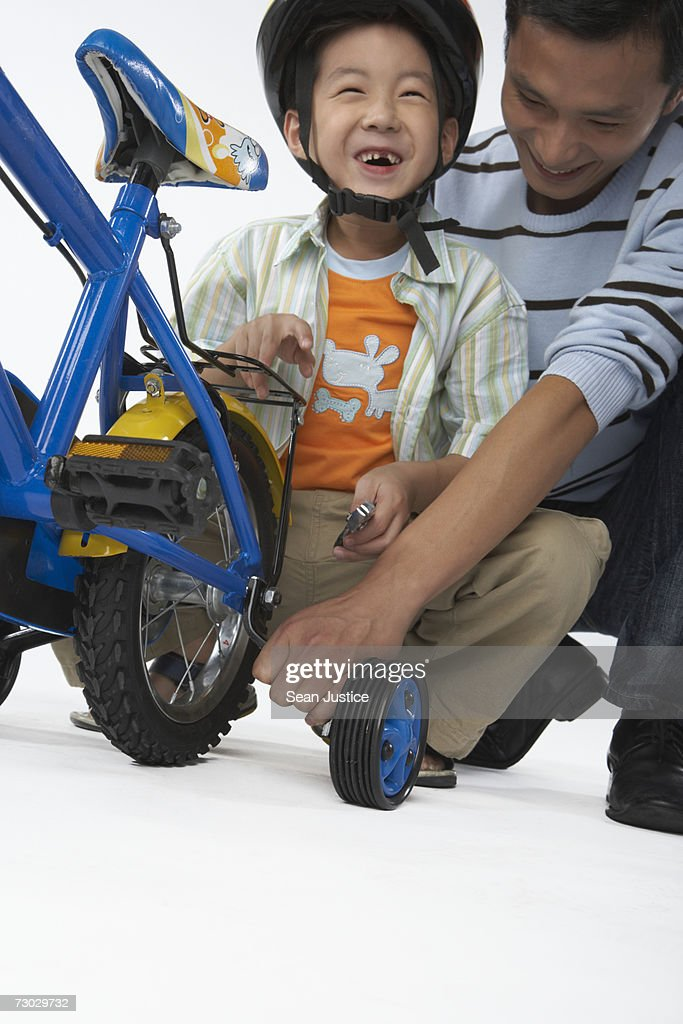 Father taking training wheels off of bike for son (6-8) : Stock Photo