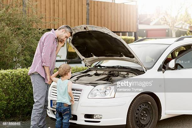 Father talking on phone and looking at car engine while standing by boy on street