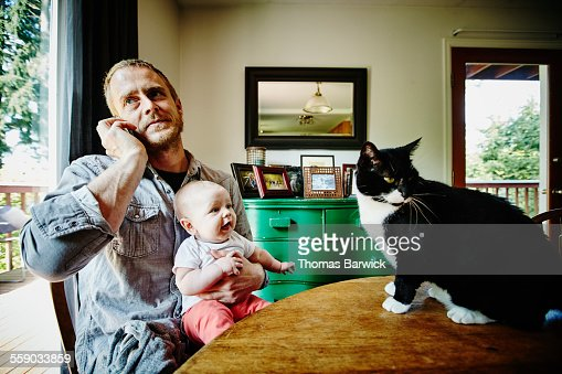 Father talking on phone while holding smiling baby