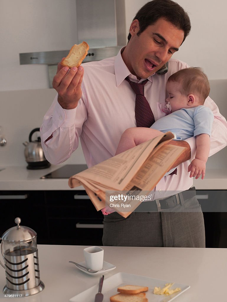 Father talking on phone with toast while holding baby daughter in a kitchen