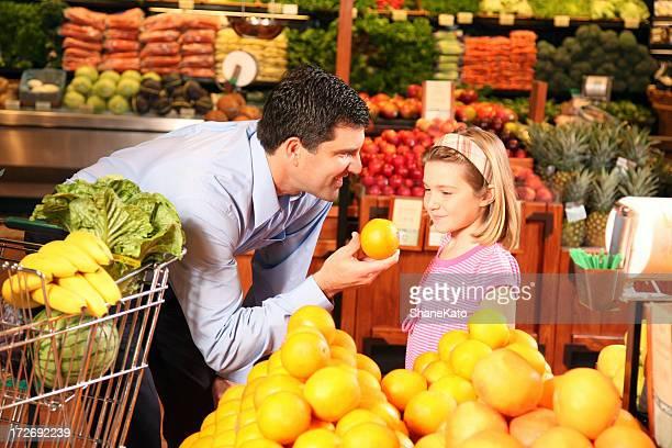 Père apprend à sa fille alimentation saine dans un supermarché de l'épicerie