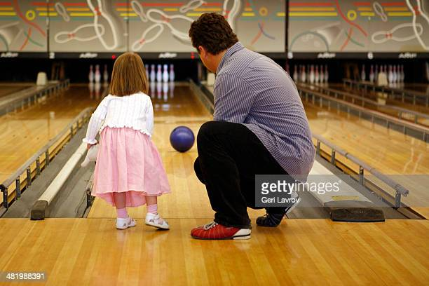 Father teaching daughter how to bowl