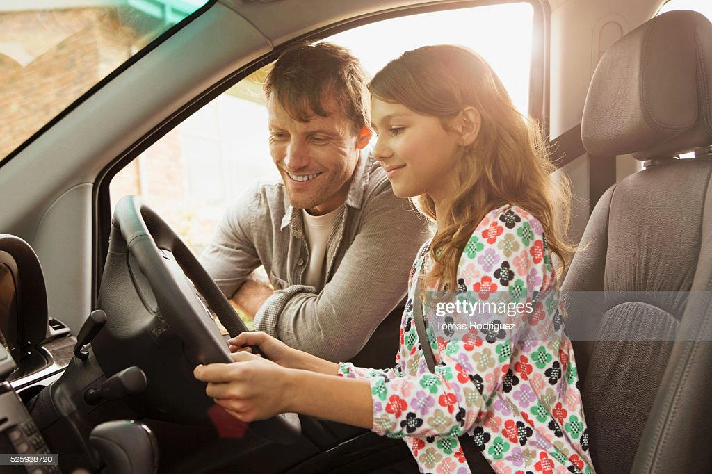 Father teaching daughter (8-9) how to drive car : Stock-Foto