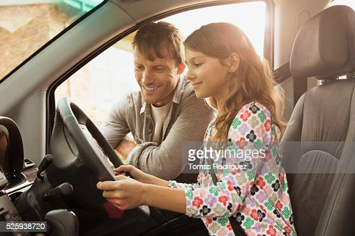 Father teaching daughter (8-9) how to drive car : Stock Photo