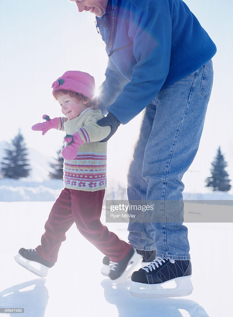 Father teaching daughter (2-4) how to ice skate, side view : Stock Photo