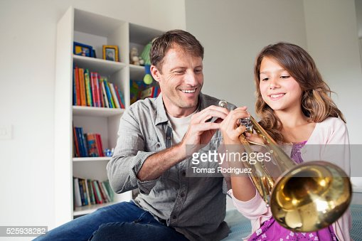 Father teaching daughter (8-9) how to play trumpet : Stock-Foto