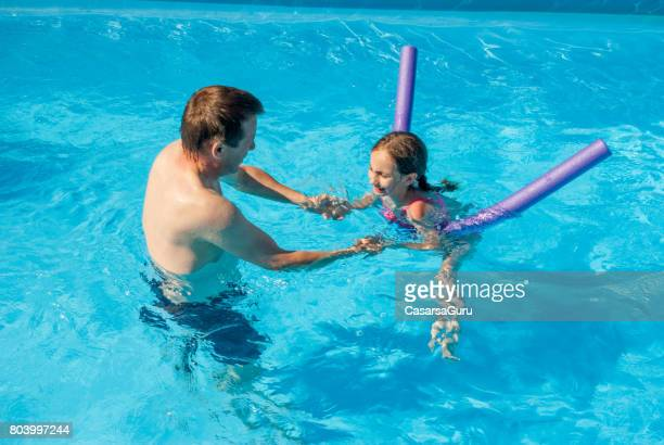 Father Teaching Daughter In The Swimming Pool How To Swim