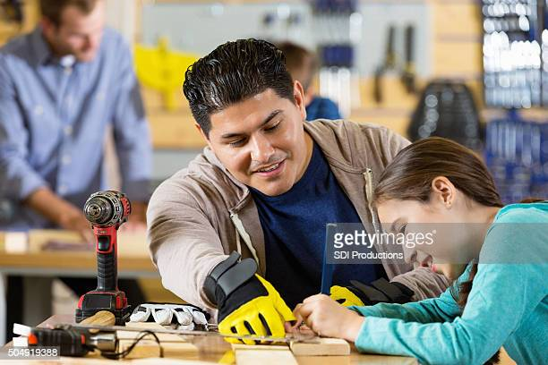 Father teaching daughter to measure boards in workshop or garage