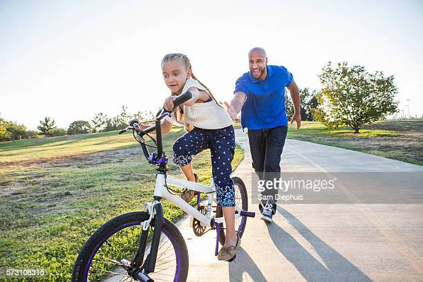 Father teaching daughter to ride bicycle in park