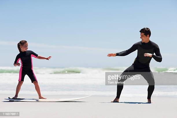Father teaching daughter to surf