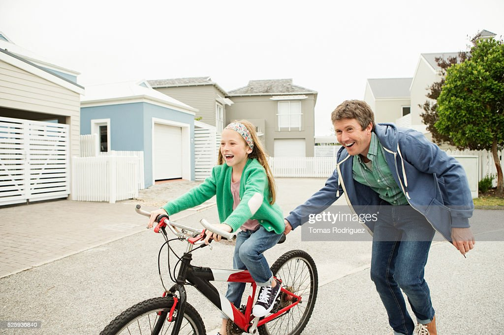 Father teaching girl (8-9) riding bicycle : Stock Photo