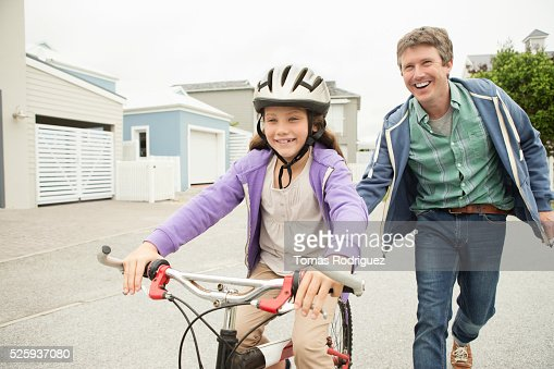 Father teaching girl (8-9) riding bicycle : Stockfoto