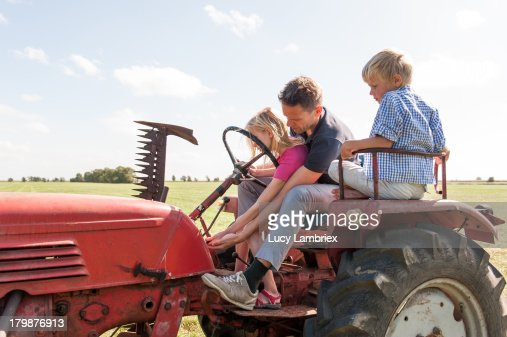 Father teaching his daughter to drive a tractor : Stockfoto