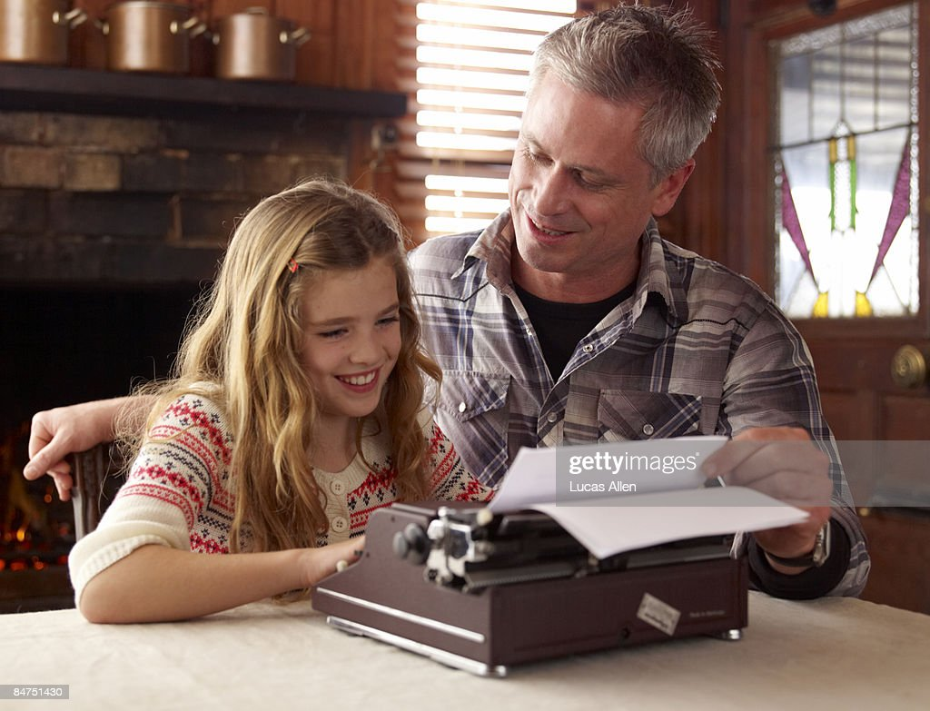 Father teaching his daughter to type : Stock Photo