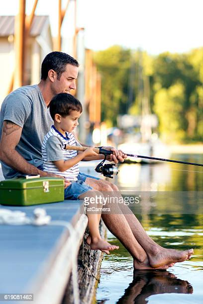 Father teaching his son how to hold a fishing rod