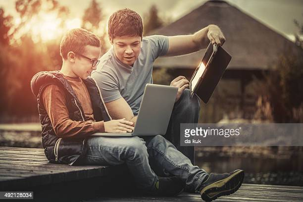 Father teaching his son how to use tablet and laptop