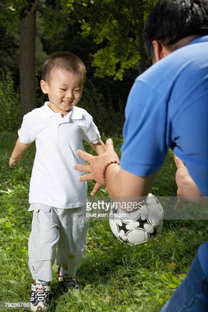 A father teaching his son soccer at the park.