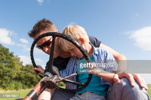 Father teaching his son to drive a tractor : Stockfoto