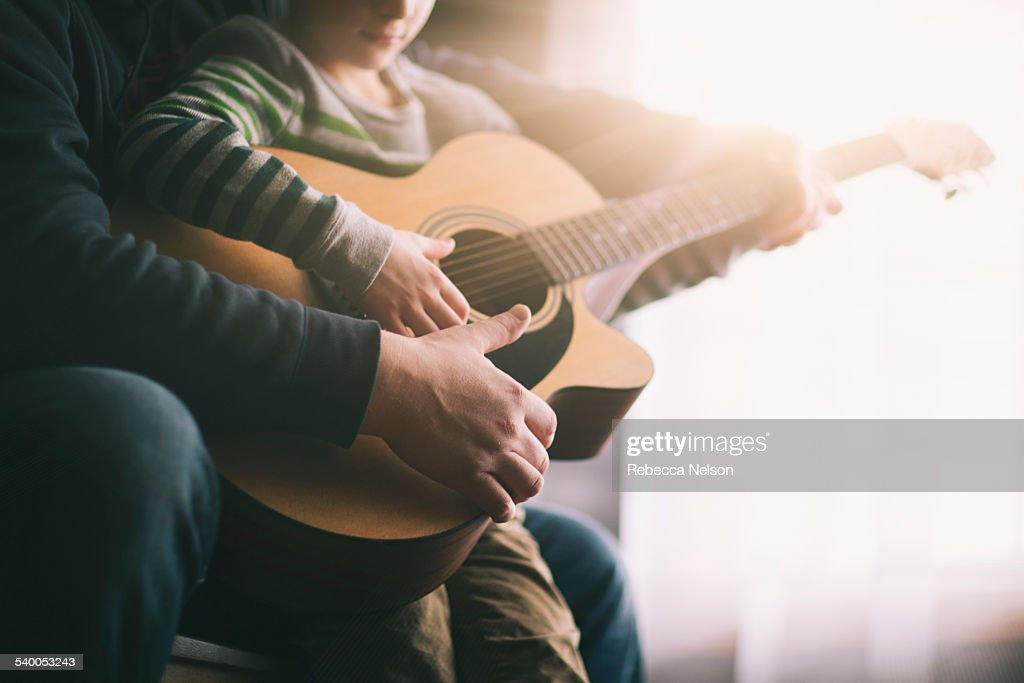 father teaching his son to play guitar : Stock Photo