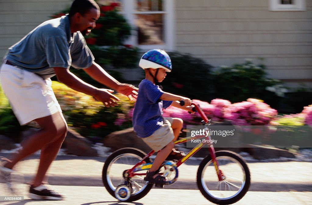 Father Teaching his Son to Ride on a Bicycle : Stock Photo