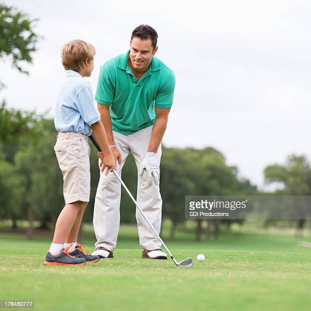 Father teaching his young son to golf