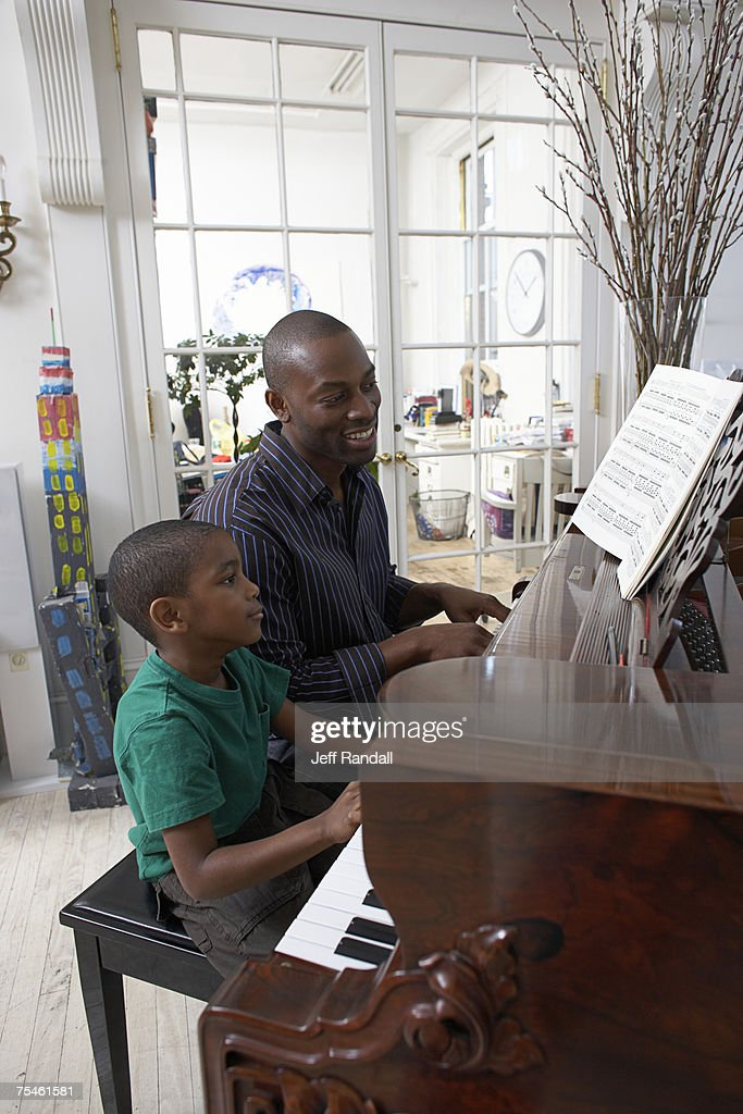 Father teaching piano to son (6-7), side view : Stock Photo