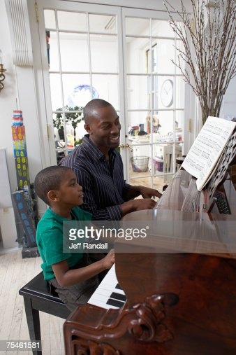 Father teaching piano to son (6-7), side view