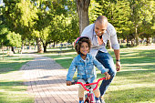 Lovely father teaching son riding bike at park. Happy father helping excited son to ride a bicycle in a summer day. Young smiling black boy wearing bike helmet while learning to ride cycle with his da