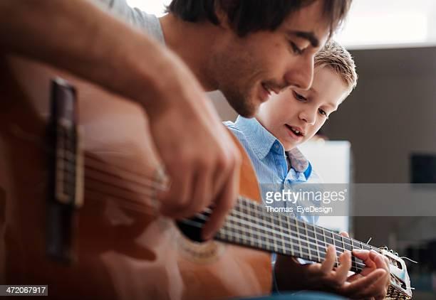 Father teaching son Guitar