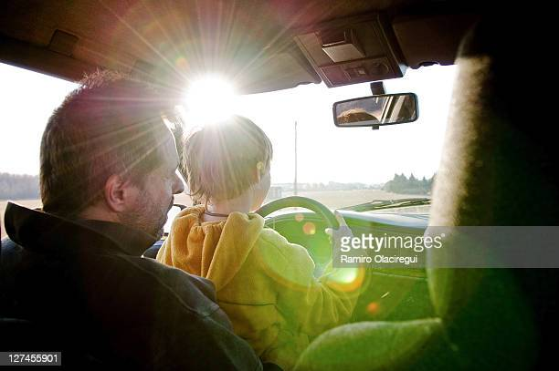 Father teaching son how to drive car