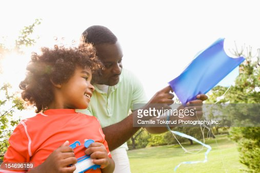 Father teaching son how to fly a kite : Stock Photo