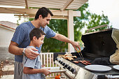 father teaching son how to grill hot dogs and bonding during the day