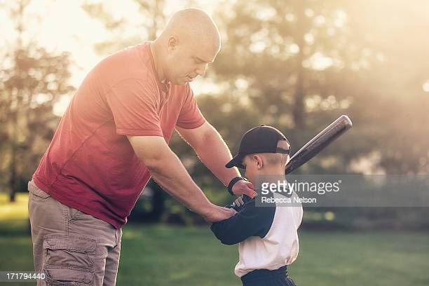 father teaching son how to hold a baseball bat