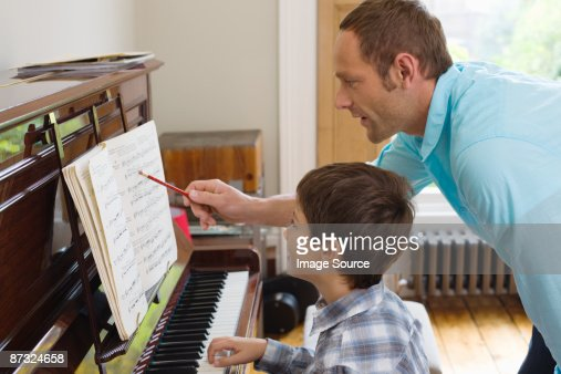 Father teaching son how to play the piano