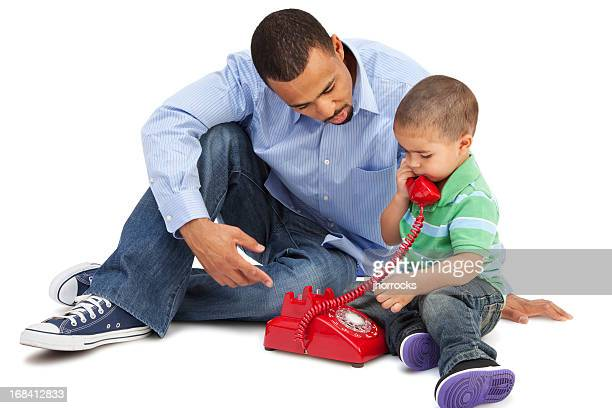 Father Teaching Son How To Use Telephone
